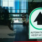 "An ""Automatic Door, Keep Moving"" sign on the glass doors of the Creekside Community Centre in Southeast False Creek"