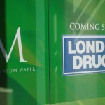 Green sign on windows of what will be the London Drugs at Millennium Water in the Olympic Village