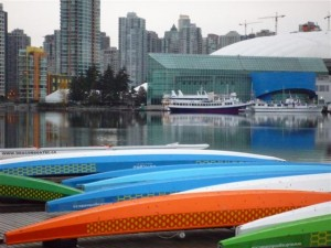 Dragonboats on dock in Southeast False Creek with Downtown Vancouver in background
